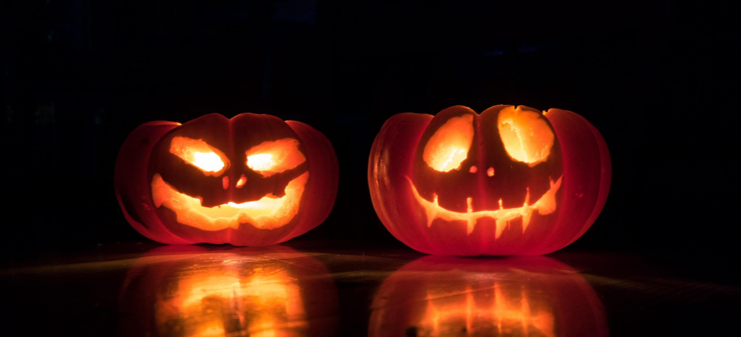 Two carved pumpkins with candlelight inside