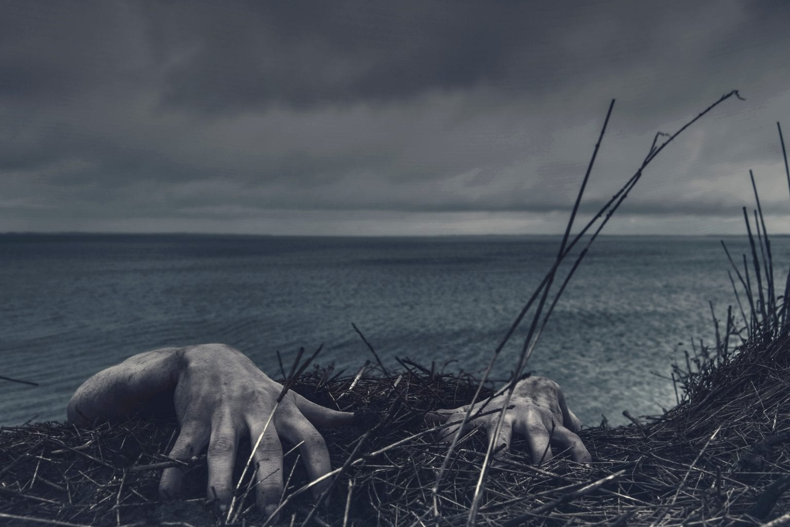 creepy zombie hands crawling up a verge