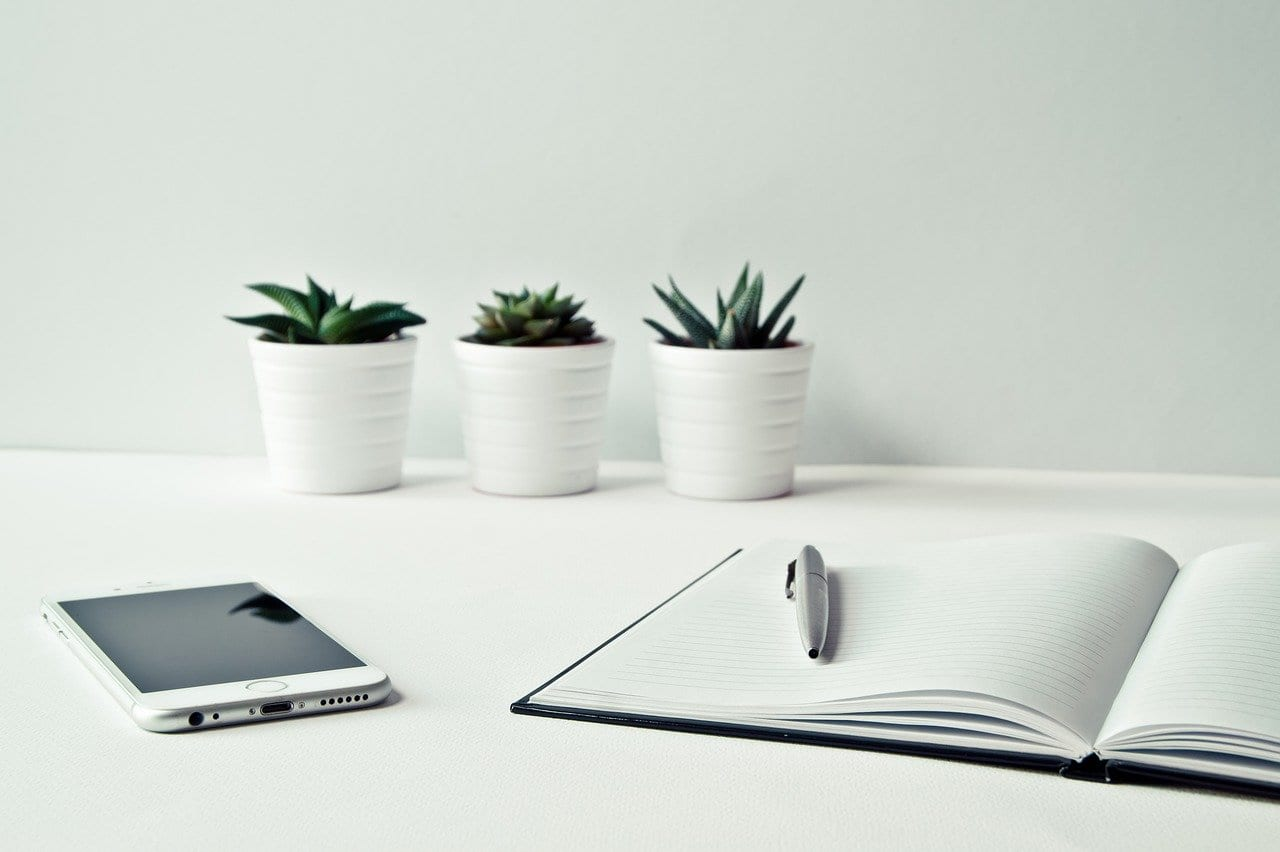 Desk with notepad, phone and plants